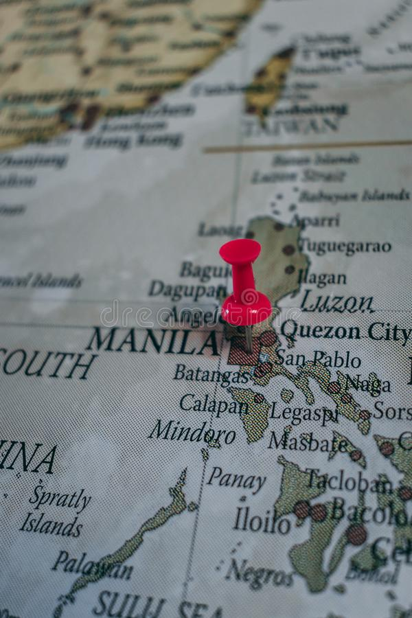 Close up of Manila pin pointed on the world map with a pink pushpin stock image