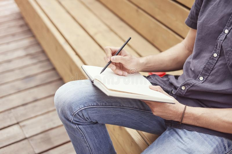 Close-up of mans hands writing in a note book sitting outside. Concept of education students youth.  stock photos