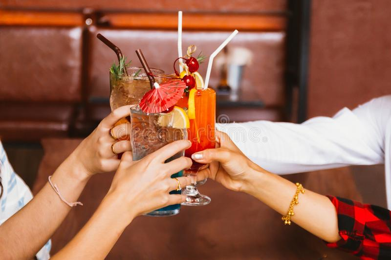 Close up of many friends hands holding a glass of alcoholic cocktail for social gathering and celebration in bar. stock images