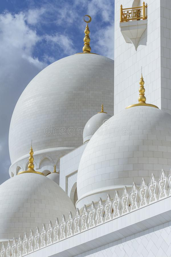 Close-up marmeren koepels met gouden pijler met Islamitisch teken op topof Sheikh Zayed Grand Mosque met blauwe hemel in de ochte stock foto