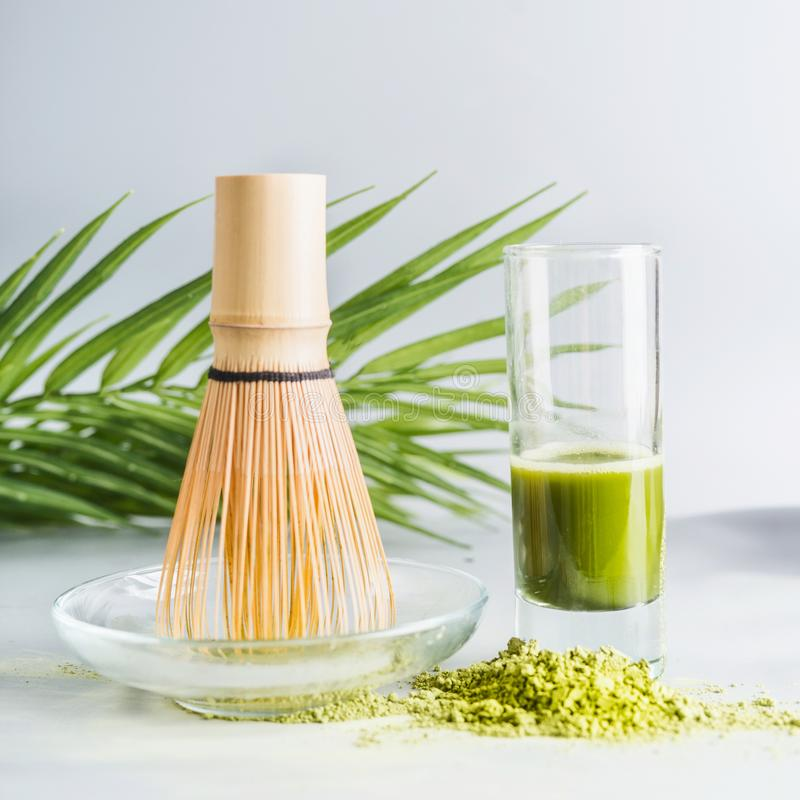 Close up of matcha espresso in glass with whisk and matcha powder on table at light background, front view with copy space. Clean. Detox beverage, healthy royalty free stock images
