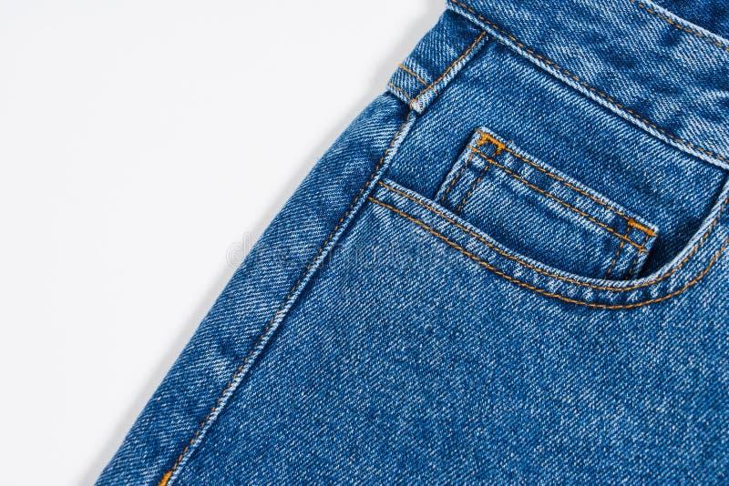 Close up material de calças de ganga de um bolso lateral Textura da sarja de Nimes no fundo branco fotografia de stock royalty free