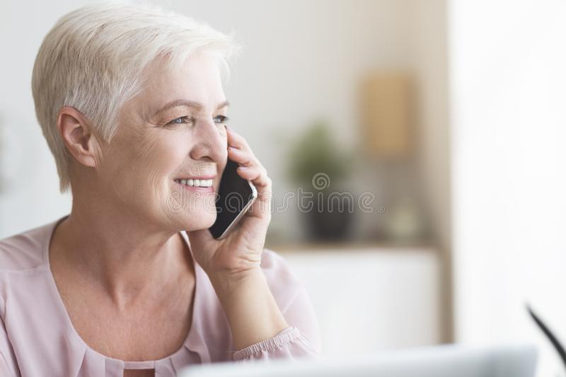 Close up of mature business woman talking by phone royalty free stock image
