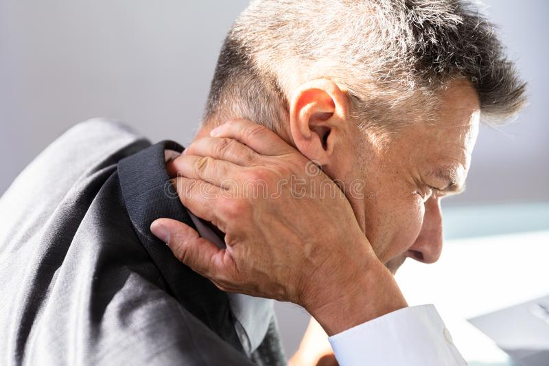 Businessman Having Neck Pain. Close-up Of A Mature Businessman Having Neck Pain royalty free stock photography