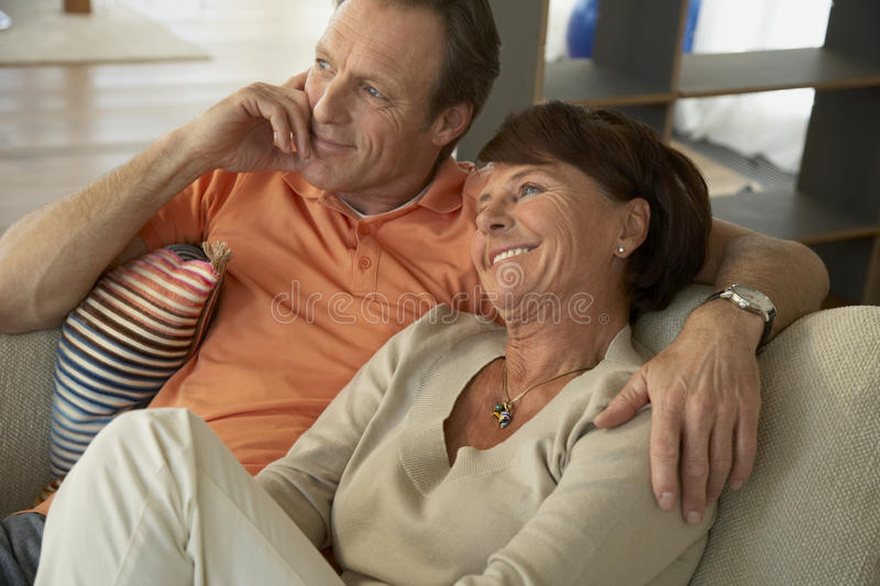 Close-up of a mature couple sitting on a couch stock photos