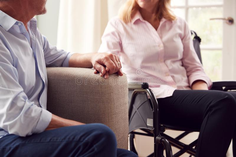 Close Up Of Mature Couple With Woman In Wheelchair Sitting In Lounge At Home Holding Hands Together stock photos