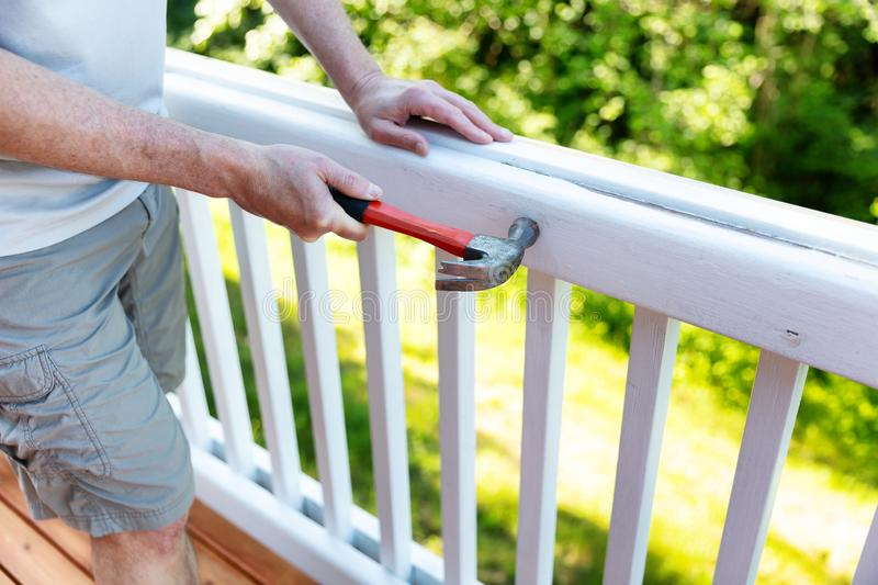 Close up of mature man hammering nail into white railing of outdoor deck stock photo