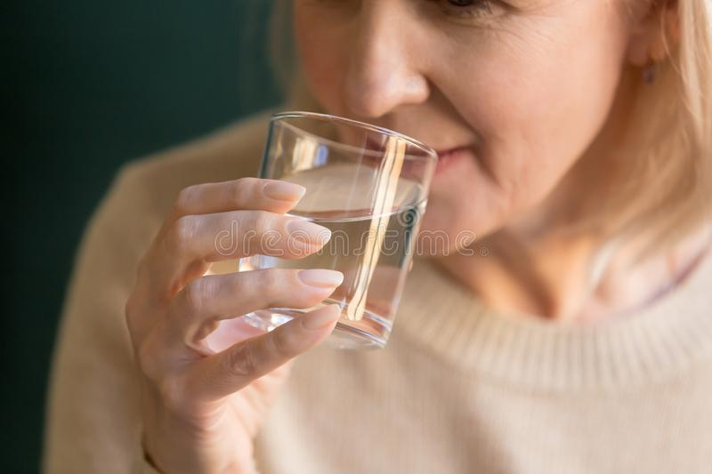 Close up of elderly woman drinking pure mineral water royalty free stock images