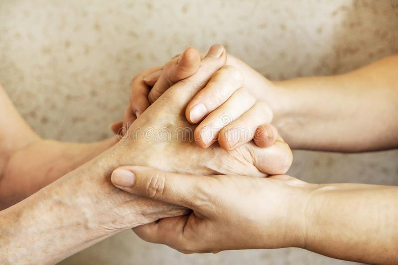 Close up of mature womans & nurse hands. Health care giving, nursing home. Parental love of grandmother. Old age related diseases. Mature female in elderly care royalty free stock images