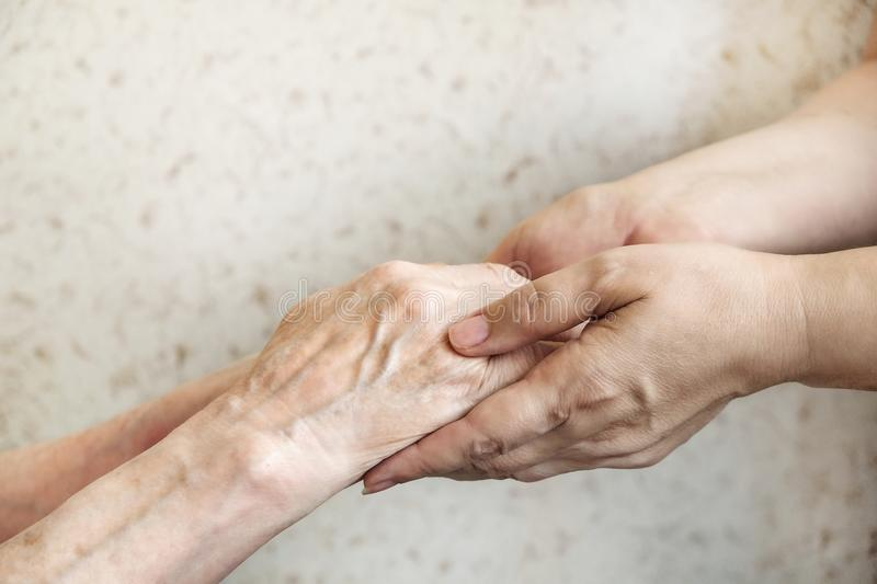 Close up of mature womans & nurse hands. Health care giving, nursing home. Parental love of grandmother. Old age related diseases. Mature female in elderly care royalty free stock photography