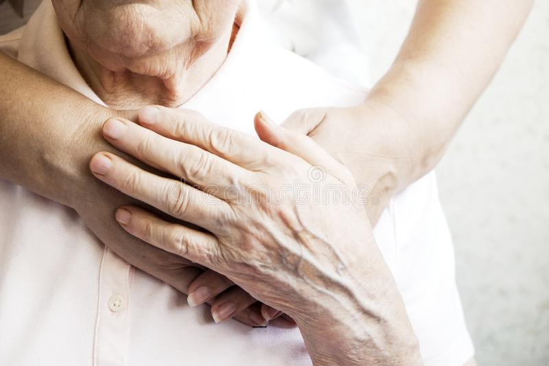 Close up of mature womans & nurse hands. Health care giving, nursing home. Parental love of grandmother. Old age related diseases. Mature female in elderly care stock images