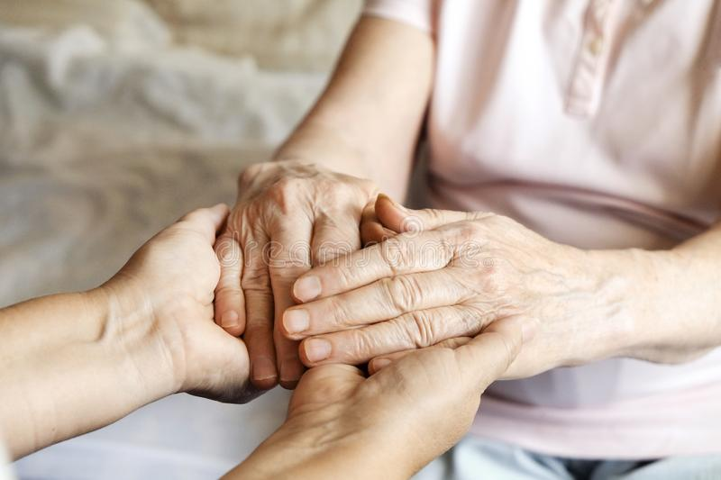 Close up of mature womans & nurse hands. Health care giving, nursing home. Parental love of grandmother. Old age related diseases. Mature female in elderly care stock photography