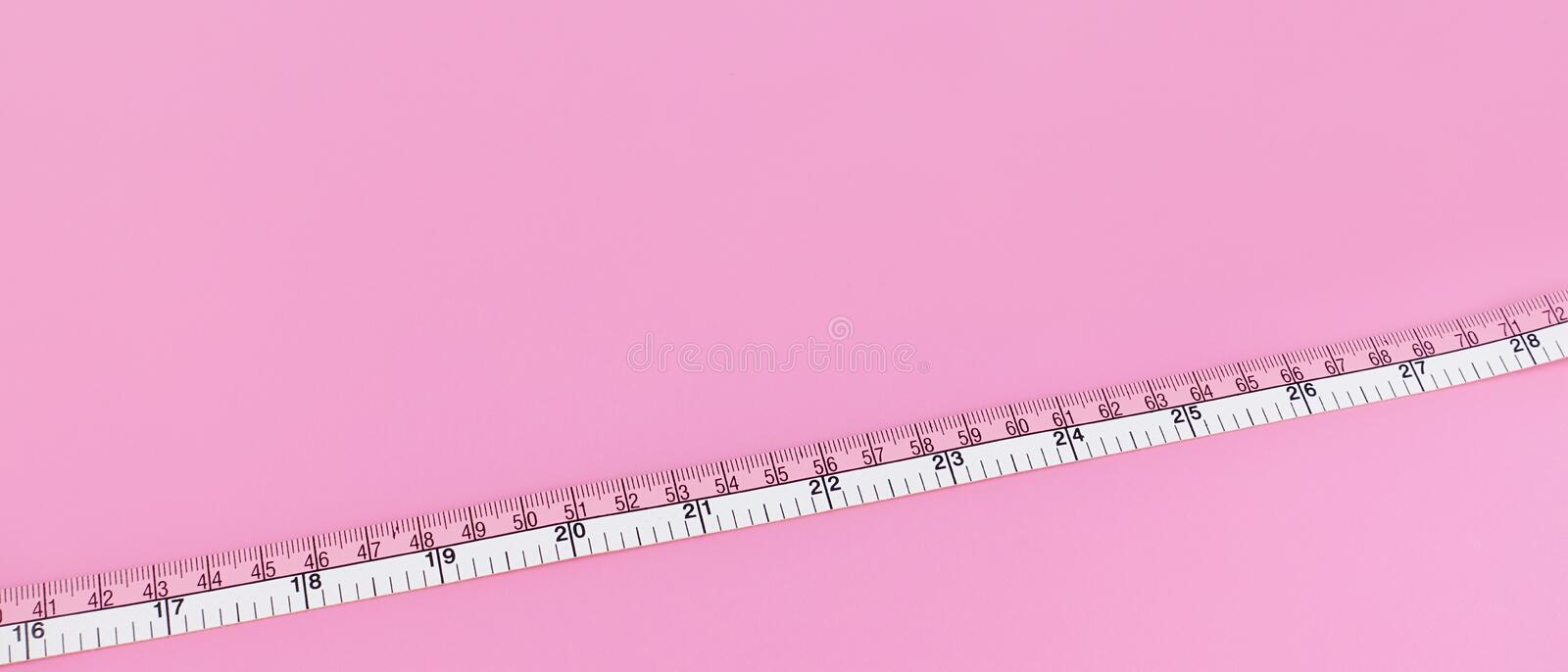Close up of measure tape. On pink background stock images