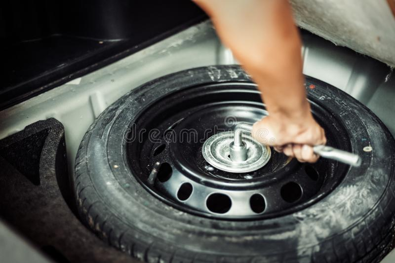 Close up mechanic hand taking spare tire at boot royalty free stock images
