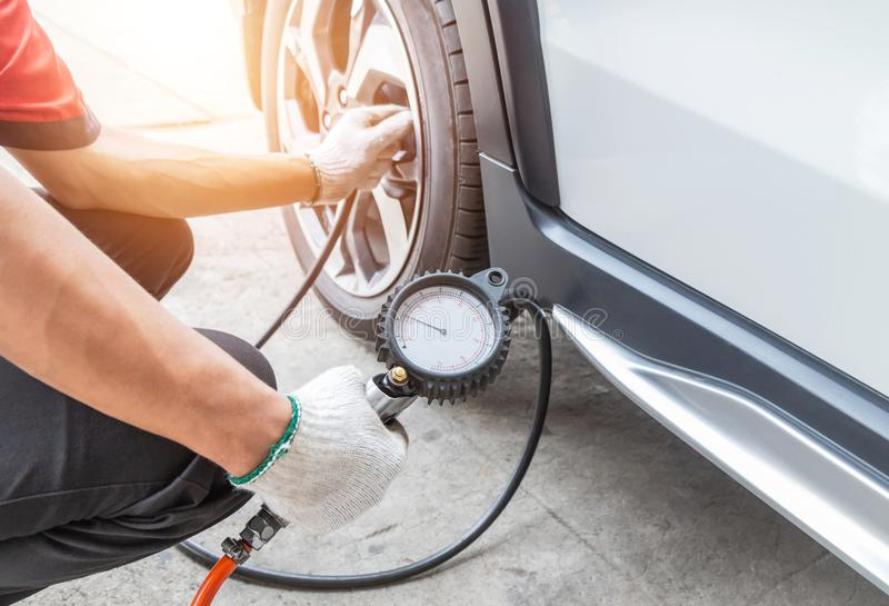 Close up mechanic inflating tire and checking air pressure with gauge pressure. In service station stock photos