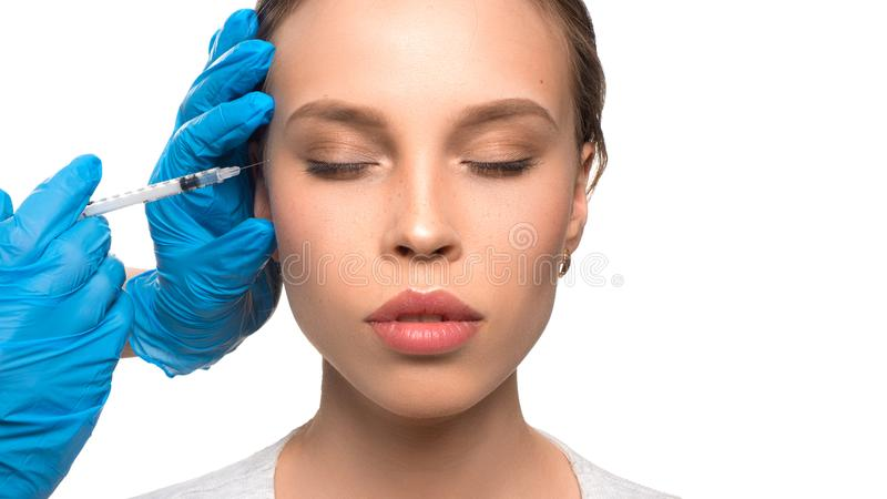 Close up of medical doctor in blue gloves injecting woman in the face with a suringe stock photo