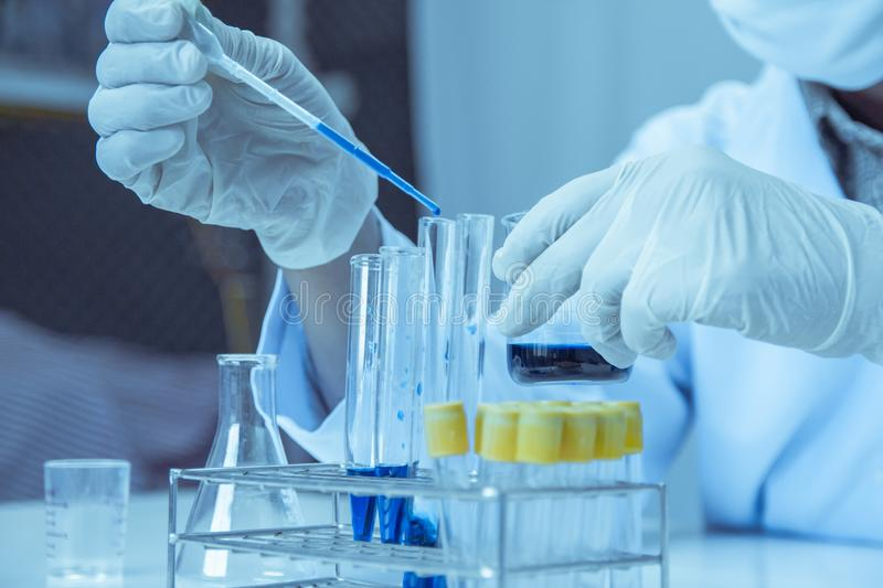 Close up. Medical or male medical in laboratory room research performs tests with blue liquid, Experimental Drug Treatment royalty free stock image