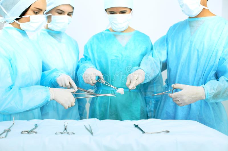 Close up of medical team in masks performing operation. Focus on surgeon`s hands using professional tools. Medicine. Emergency help concepts stock images