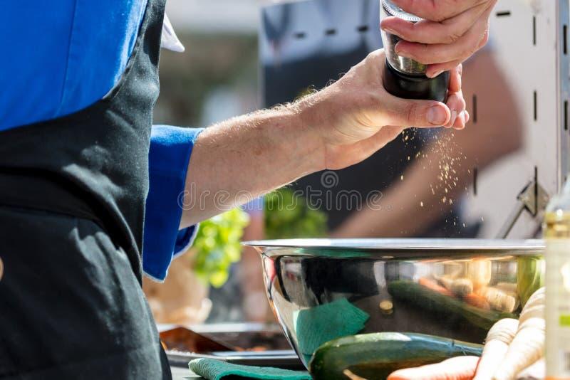Close-up medio sectie van een chef-kok die zout en Peper in de keuken zetten royalty-vrije stock fotografie