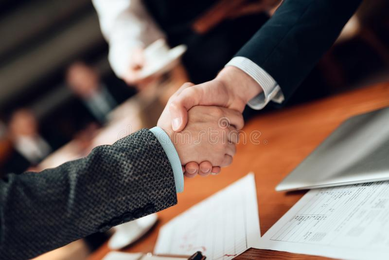 Close up. Meeting with chinese businessmen in restaurant. Men are shaking hands. royalty free stock photo