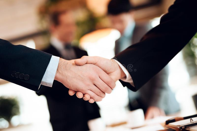 Close up meeting with chinese businessmen in restaurant. Men are shaking hands. stock photo