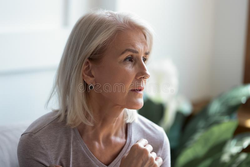 Close up image serious pensive sad aged female. Close up melancholic 60s elderly woman looks away face lit by sunlight when feels hurt and lonely, pensive old royalty free stock photos