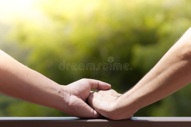 Close up of men gay couple holding hands on green natural background. royalty free stock photo
