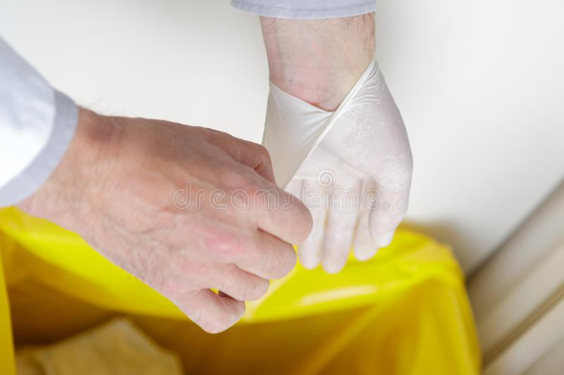 Close-up man removing latex gloves from hands into dustbin. Close-up of men removing latex gloves from hands into dustbin royalty free stock image