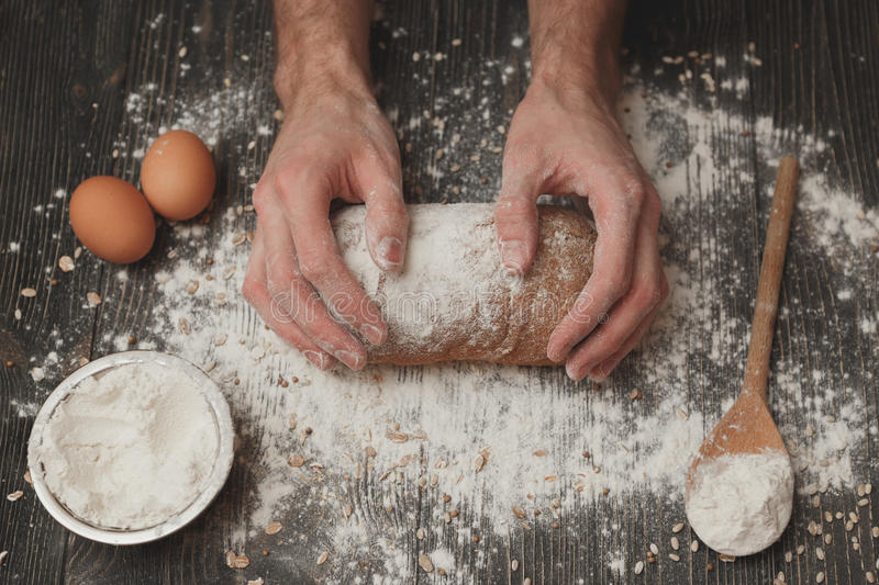 Close-up of men`s baker hands on black bread with flour powder. Baking and patisserie concept royalty free stock photo