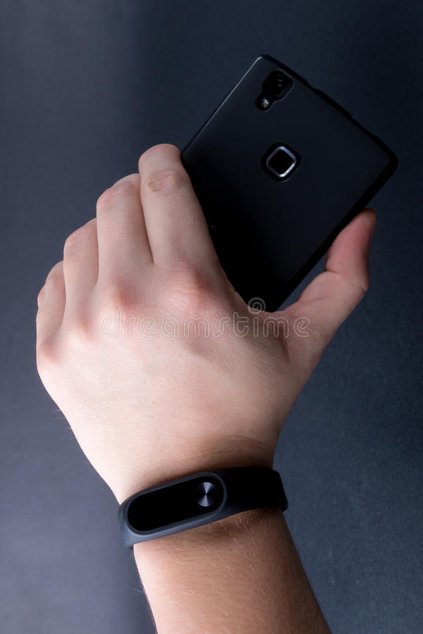 Close up of men's hand with a sports bracelet and smartphone on black background. stock photo