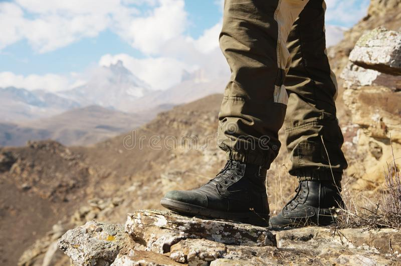 Close-up of men`s legs in hiking boots against the background of rocks and distant Caucasian epic mountains of lands royalty free stock image