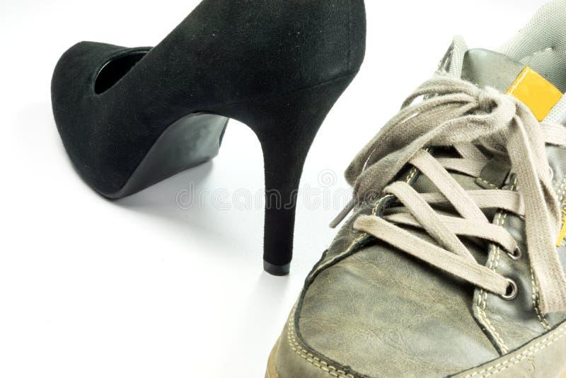 Men`s shoe and a high heel women`s shoe. Close up of men`s shoe and a high heel women`s shoe stock photography