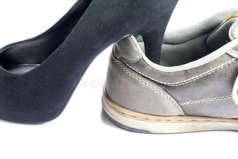 Men`s shoe and a high heel women`s shoe. Close up of men`s shoe and a high heel women`s shoe royalty free stock photography