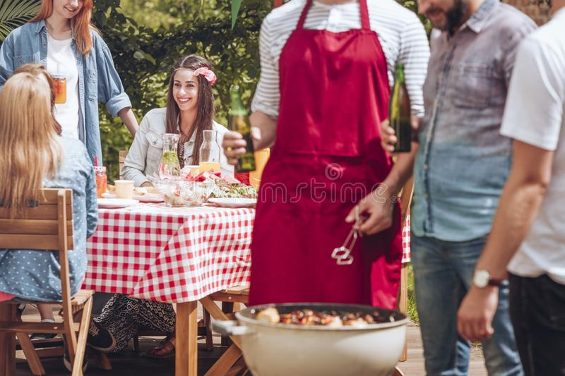 Close-up of men standing and talking over a grill with shashliks. Beautiful woman sitting by a birthday party table in. Close-up of men standing and talking over royalty free stock images
