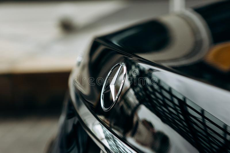 A close-up of the Mercedes sign and the back of the new luxury black Mercedes-Benz car. Berlin, August 29, 2018: A close-up of the Mercedes sign and the back of royalty free stock photography
