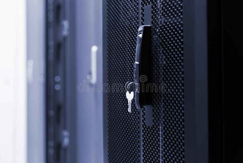 Close up meshed door with key in lock. Button in server room. Blur background of racks rows with network and hardware in the data. Close up meshed door with key royalty free stock images