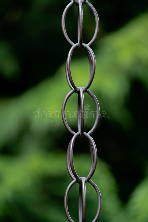 Close up of metal chain links. And a blurry green bokeh background royalty free stock image