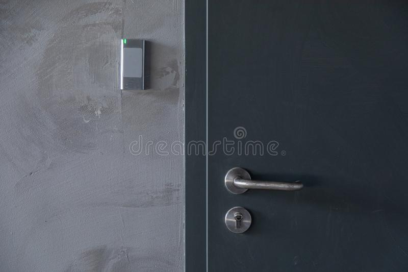 Close-up of metal door with signalization in grey concrete wall. Close-up of metal door with access control in grey concrete wall royalty free stock image