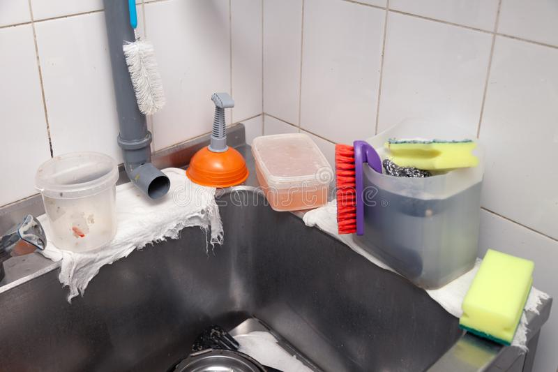 Close-up of a metal sink in the professional kitchen of the restaurant, orange plunger, pipe, faucet, container with dishwashing. Closeup of a metal sink in the stock photos