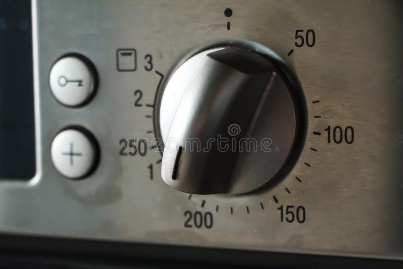 A close-up of a metal temperature and mode switch on the oven indicates a temperature of 180 degrees, selective focus. Copyspace stock image