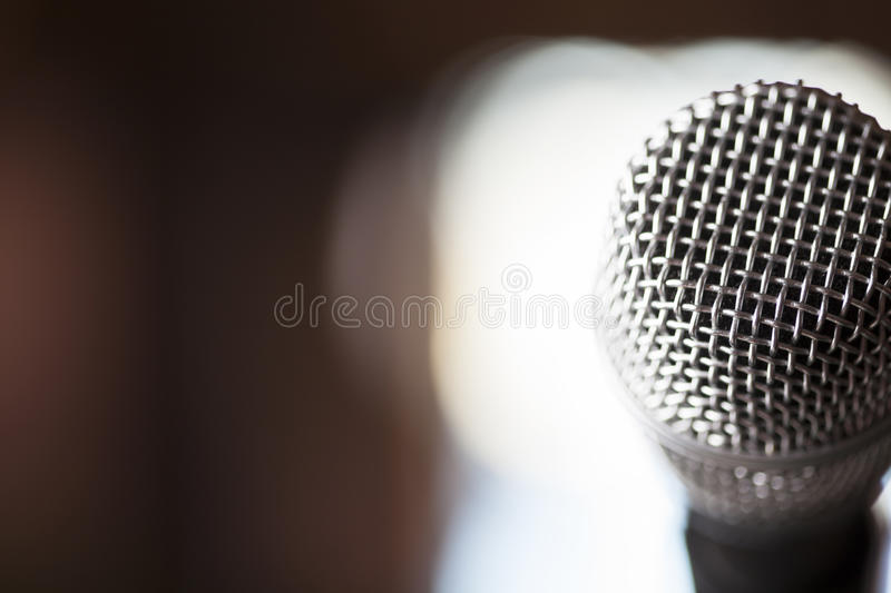 Close Up Microphone Background. A macro shot of a silver microphone with light in the backround stock photography
