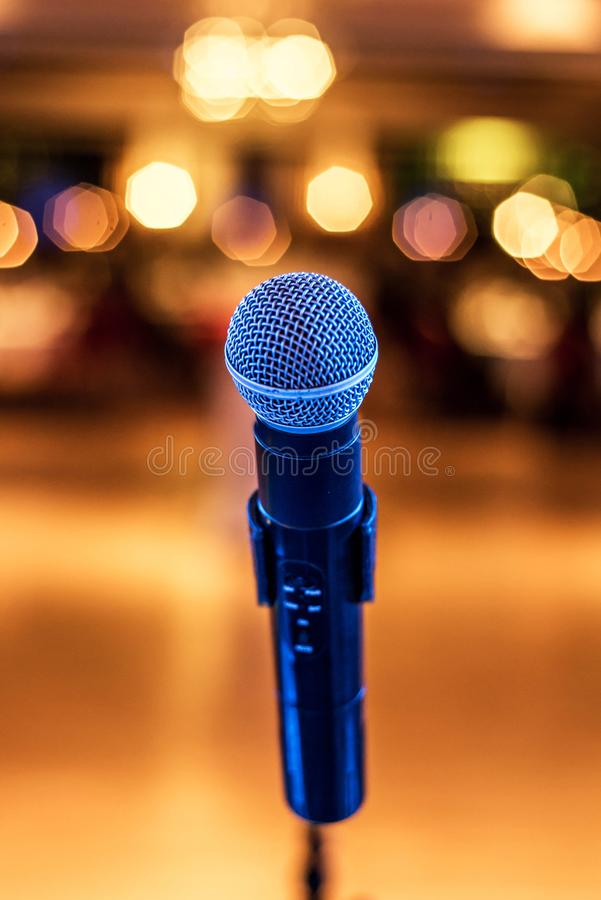 Close up of microphone in concert or conference hall with blurred lights at background. Close up of microphone in concert hall with blurred lights at background royalty free stock images