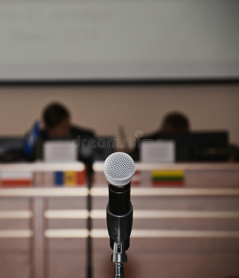 Close up of microphone in concert hall or conference room. Close up of one microphone in concert hall or conference room stock photo