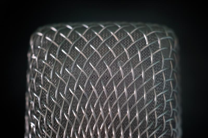 Close-up of the microphone grille of steel wire on a black background. Macro shooting with shallow depth of field. The concept of stock photos