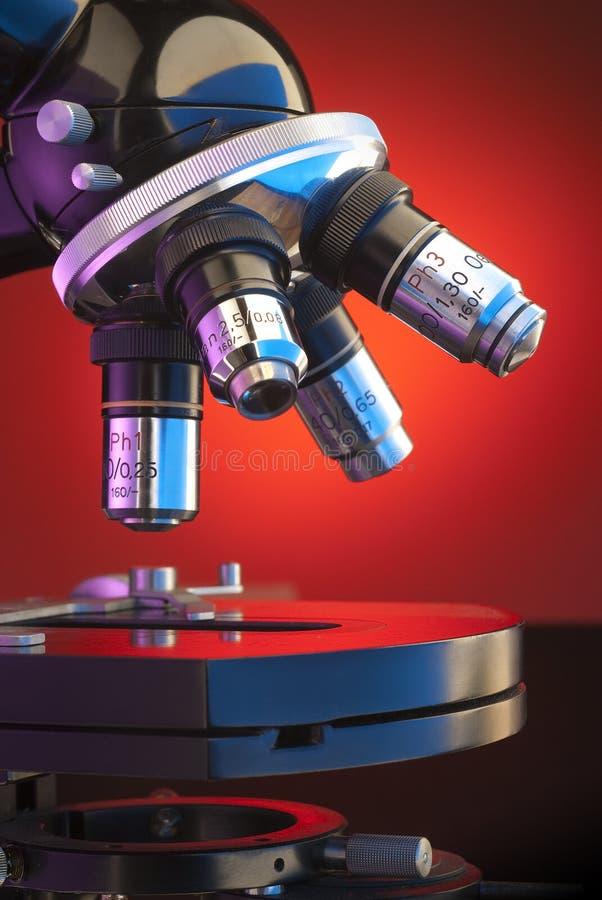 Close up of microscope turret and platen. Close up shot of four lens microscope turret back lit by orange spot light royalty free stock photo
