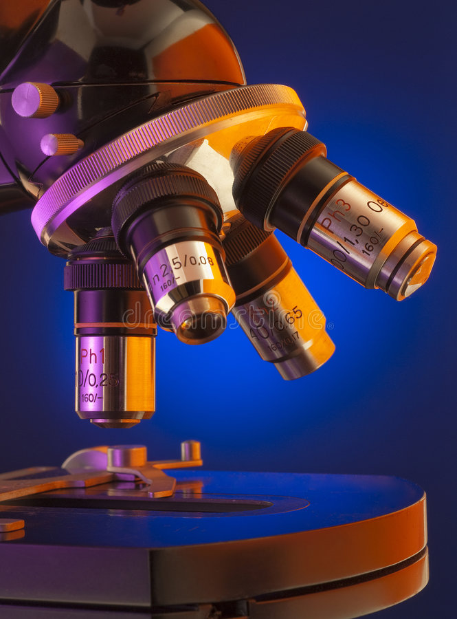 Close up of microscope turret and platen. Close up shot of four lens microscope turret back lit by blue spot light stock image