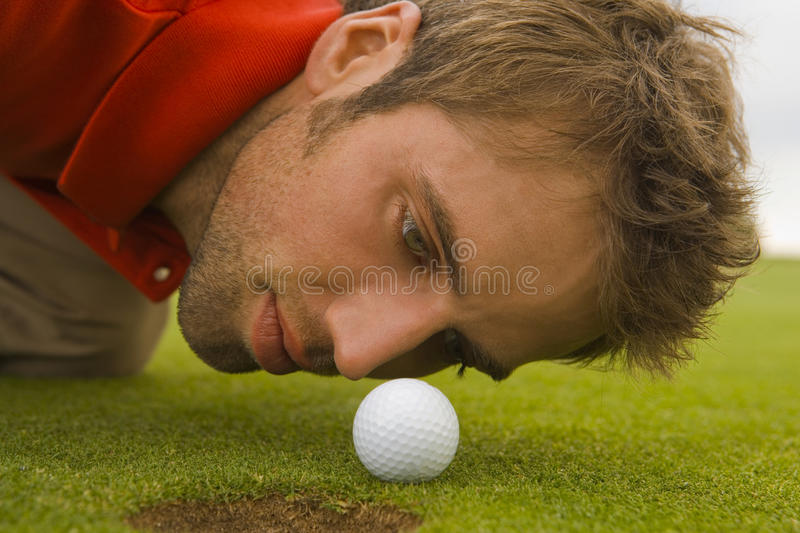 Close-up of a mid adult man judging a golf ball. royalty free stock photos
