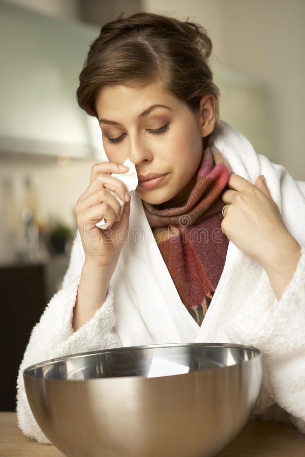 Close-up of a mid adult woman sitting in front of a wash bowl.  stock photography