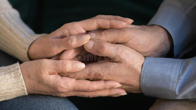 Close up aged wife holding husband hands, showing support, love. Close up middle aged wife holding husband hands, showing support and love, expressing sympathy royalty free stock photos