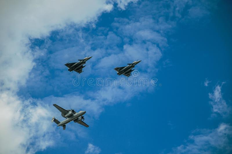 Close-up of military aircraft passing through the overcast sky of Paris. royalty free stock images